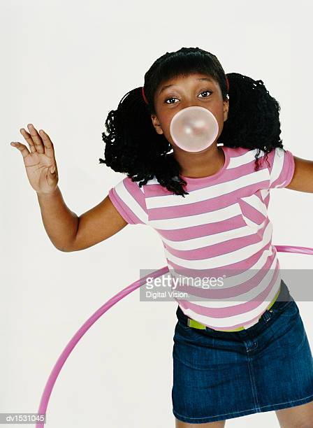 Girl in a Striped T-Shirt Plays With a Hoop and Blows Gum