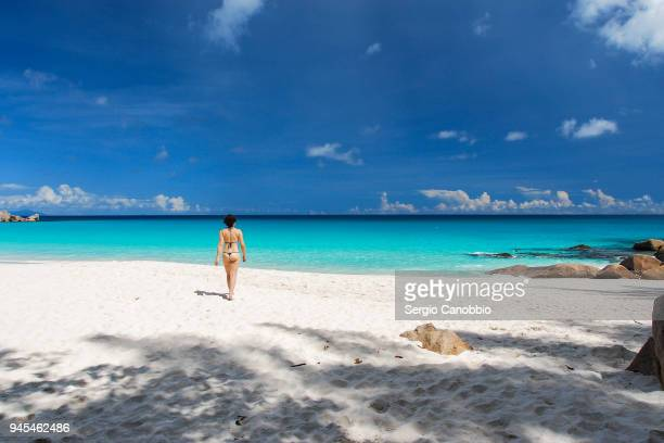 girl in a thong bikini walking in anse georgette - thong bikini stock pictures, royalty-free photos & images
