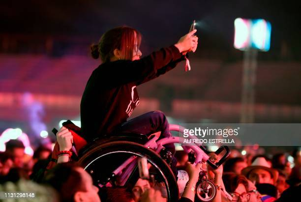 A girl in a wheelchair is lifted up so that she can take a picture of Colombian singer and composer Juanes as he performs during the second day of...