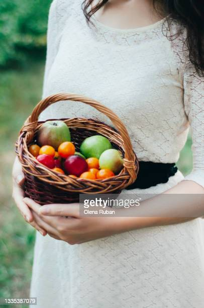 girl in a white dress holds a basket of diverse fruits - luggage hold stock pictures, royalty-free photos & images