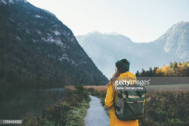 girl in a yellow jacket with a backpack in a green hat looks at the mountains rear view close-up - wandern stock-fotos und bilder