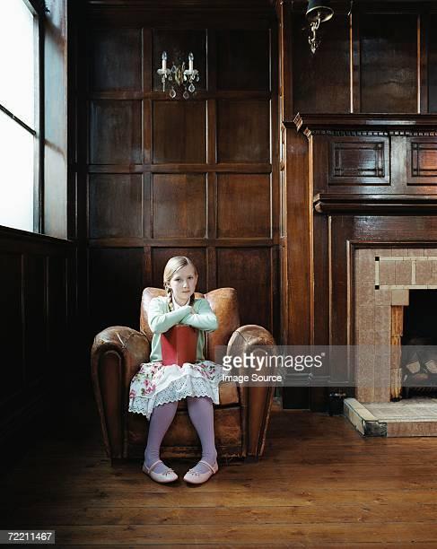 Mädchen in einen Sessel mit einem Buch