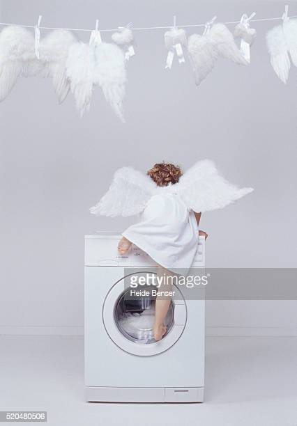 Girl in angel costume climbing onto washing machine