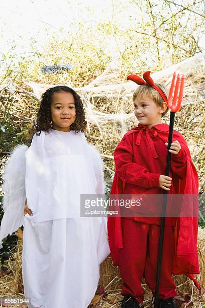 girl in angel costume with boy in devil costume - devil costume stock photos and pictures