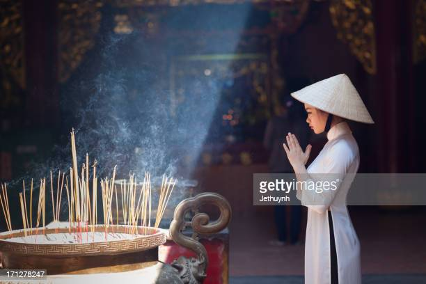 a girl in ao dai praying in a pagoda - ho chi minh city stock pictures, royalty-free photos & images