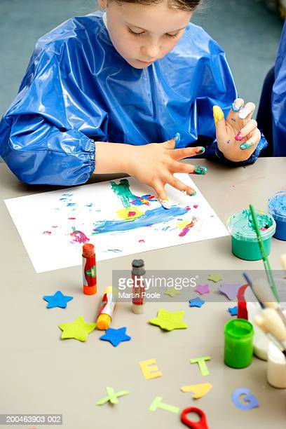 Girl (6-8) in art class painting with fingerprints, elevated view