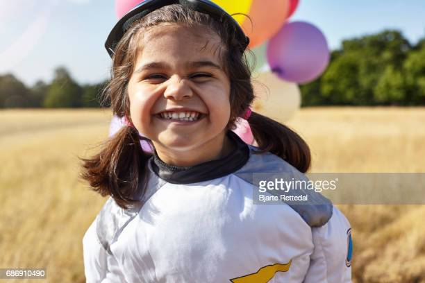 Girl in Astronaut Suit grinning to camera
