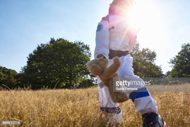 Girl in Astronaut Suit running through field