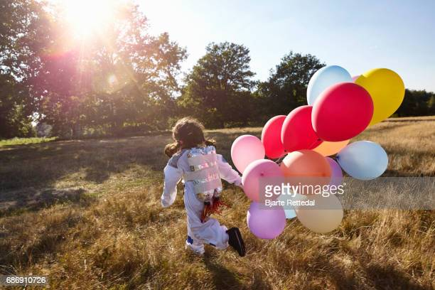 Girl in Astronaut Suit with jet pack running through field