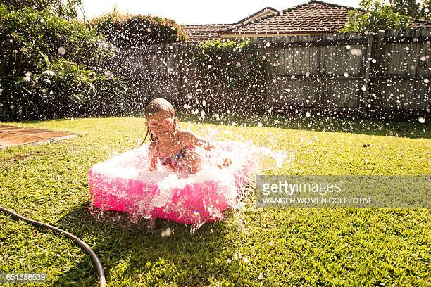 Girl in Australian backyard baby pool splashing