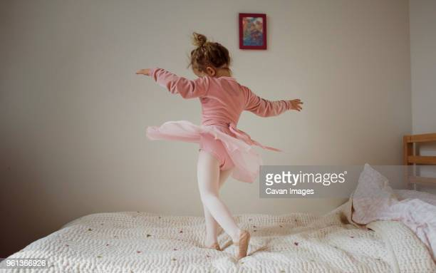 girl in ballet costume dancing on bed at home - ballet stock pictures, royalty-free photos & images