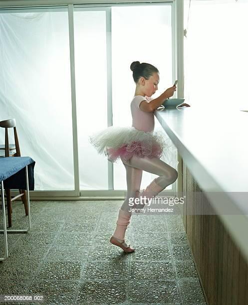 Girl (7-9) in ballet costume eating from bowl