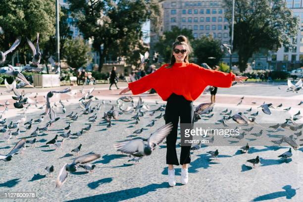 Girl in Barcelona jumping among the pigeons