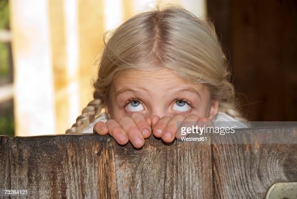 Girl (7-9) in barn, rolling eyes, close-up