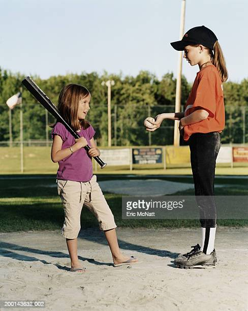 girl (8-10) in baseball uniform showing younger girl (6-8) baseball - sports bat stock pictures, royalty-free photos & images