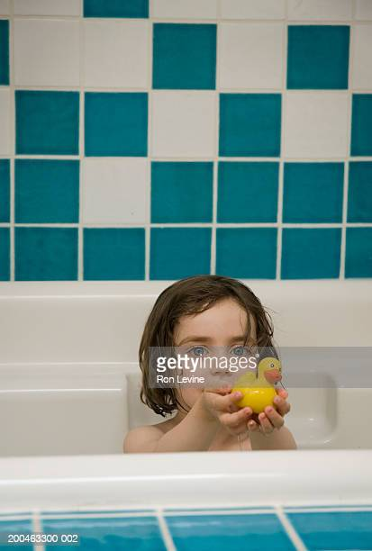 Girl (2-4 years) in bath, holding rubber duck, portrait