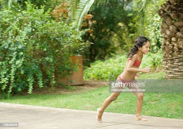 Girl in bathing suit running in back yard