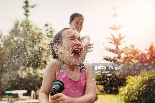 girl (4-5) in bathing suit sprayed with water hose. - istantanea foto e immagini stock