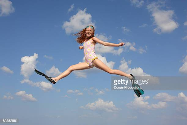 girl in bathing suit with flippers jumping - legs apart stock photos and pictures