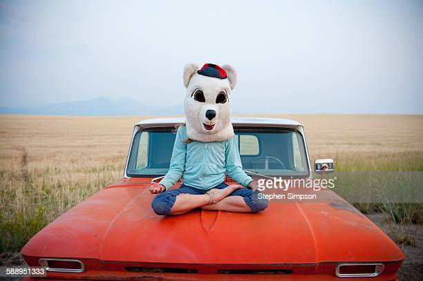 girl in bear costume doing yoga on old truck - animal costume stock pictures, royalty-free photos & images