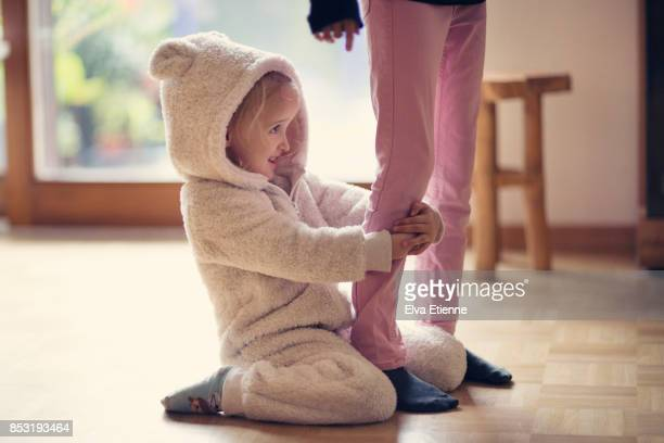 Girl (4-5) in bear suit onesie, pulling another child's leg