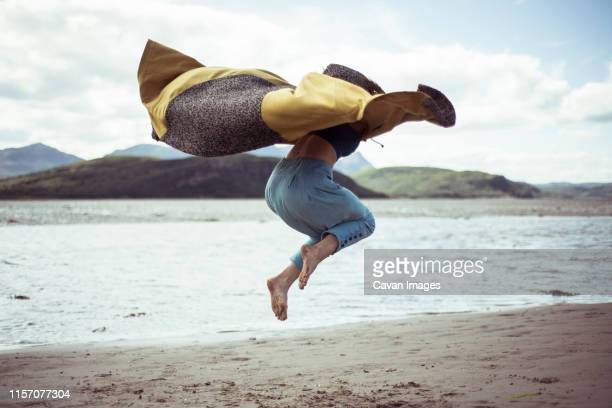 girl in beautiful cloak jumps on beach - flowing cape stock pictures, royalty-free photos & images
