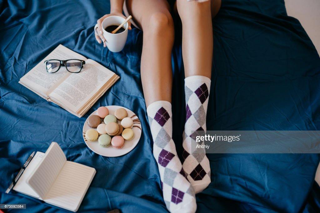 コーヒーを飲みながら、クッキーを食べてベッドで女の子 : ストックフォト
