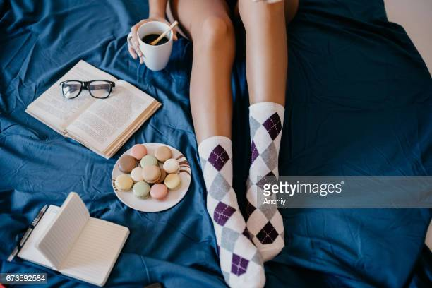 Girl in bed drinking coffee and eating cookies