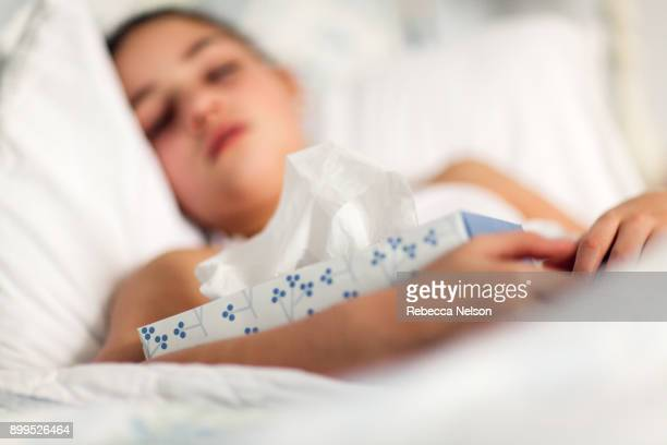 Girl in bed holding box of tissues