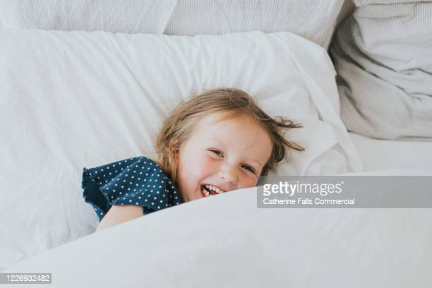 girl in bed - hotel stock pictures, royalty-free photos & images