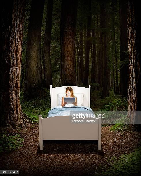 girl in bed reading in forest - sprookjesboom stockfoto's en -beelden