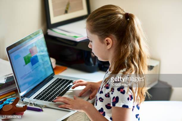 girl in bedroom doing online homework during lockdown - computer stock pictures, royalty-free photos & images
