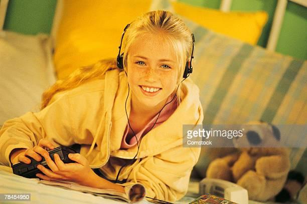Girl in bedroom listening to music with headphones