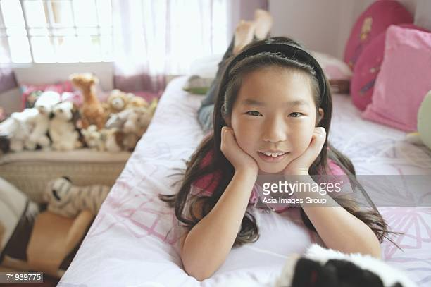 Girl in bedroom, lying on bed, hands on chin, looking at camera