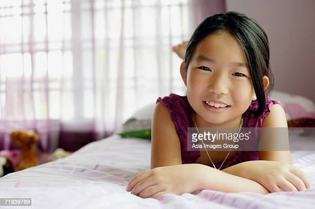 Girl in bedroom, lying on bed, smiling at camera