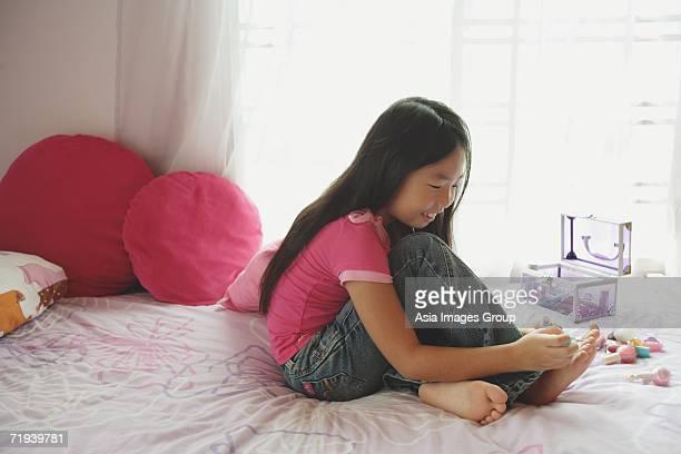 Girl in bedroom, painting toenails, side view