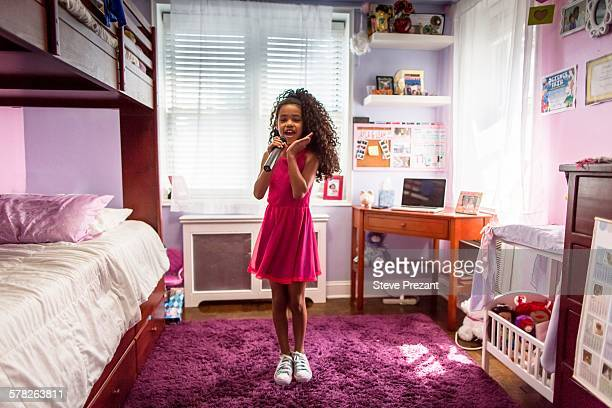 Girl in bedroom singing into microphone and dancing
