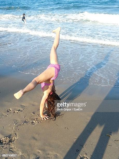 girl in bikini doing gymnastics at beach - little girls doing gymnastics stock photos and pictures