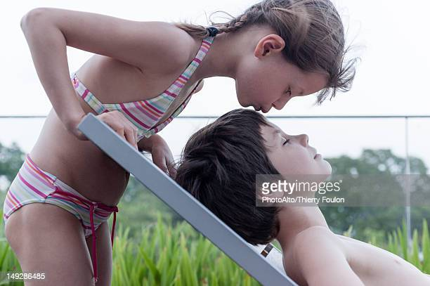 Girl in bikini kissing brother reclining on deckchair