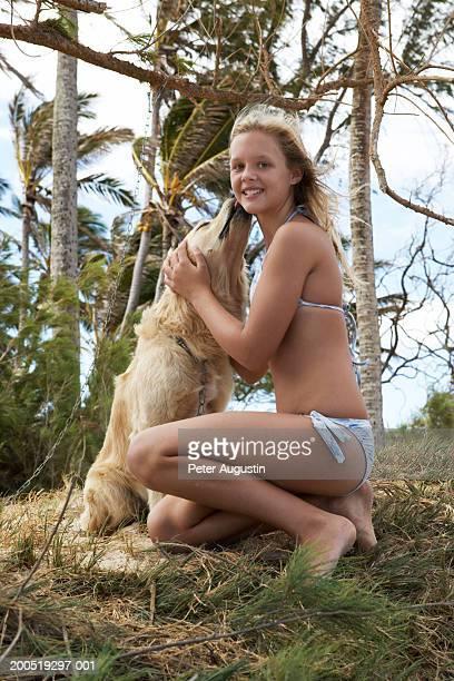 Girl (9-11) in bikini kneeling beside golden retriever, portrait