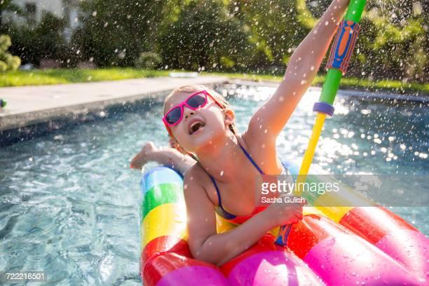 Girl in bikini on inflatable playing with water gun in outdoor swimming pool