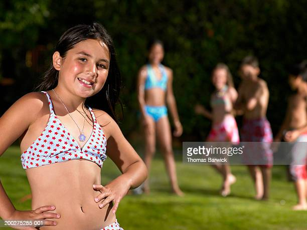 Girl in bikini standing near other children (9-10), smiling, portrait
