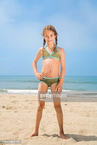 girl (9-11) in bikini standing on beach, hand on hip, portrait - 8 9 anos - fotografias e filmes do acervo