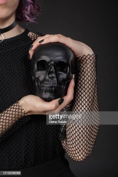 girl in black clothes holding black skull - mort concepts photos et images de collection