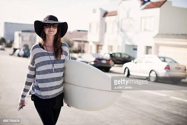 Girl in black hat walking w/surfboard & cell phone