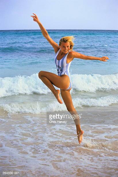 Girl in blue and white striped swimsuit running along shore