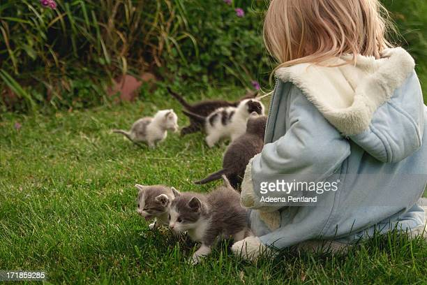 Girl in blue coat sitting with six tiny kittens