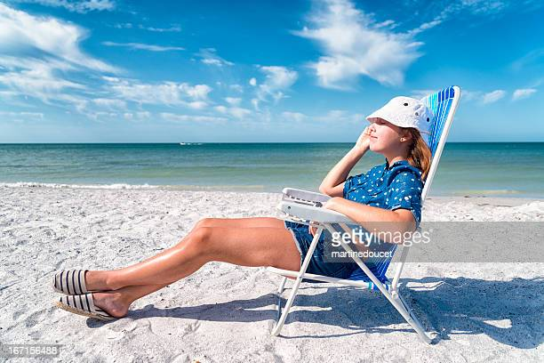 "girl in blue relaxing on the beach, horizontal. - ""martine doucet"" or martinedoucet stock pictures, royalty-free photos & images"
