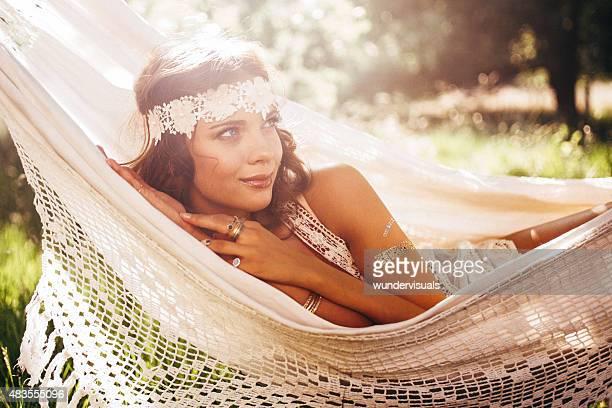 Girl in boho fashion daydreaming in a hammock in summer