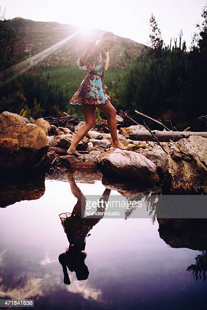 Girl in boho floral dress stepping over stones at lake